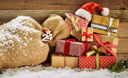 Colorful Christmas still life with wrapped gifts topped with a red Santa hat and a burlap sack in winter snow against a wooden wall