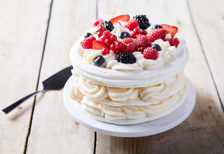 Gourmet pavlova cake with fresh berry topping and layers of whipped cream and meringue served on a plate with a spatula in a close up view 版權商用圖片