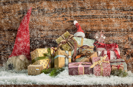 Colorful pile of decorative Christmas gifts in a winter snow fall with red Santa hats outdoors nestling in the snow against rustic wood with copy space