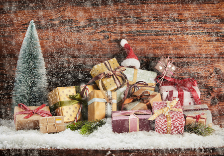 Winter snow falling on a pile of Christmas gifts in colorful wrapping with ribbons and bows against rustic vintage wood background with copy space 版權商用圖片