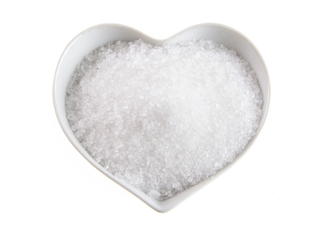 Fleur de sel in a heart-shaped bowl isolated on white, a sea salt formed by evaporation at the surface of the water Stock Photo