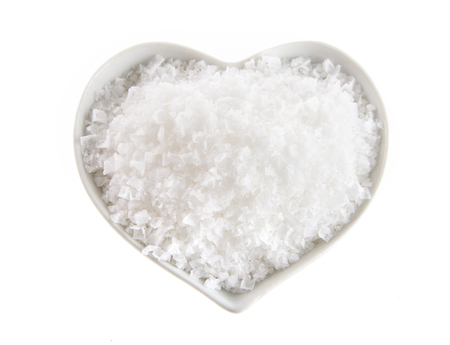 Heart shaped bowl of Flor de Sal, a Portuguese salt derived from the evaporation of sea water, viewed from above isolated on white Stock fotó