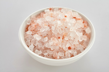 Bowl of coarse pink Himalaya salt, a rock salt or halite used for seasoning food, over a white background