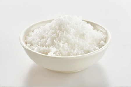 Small dish of clean white Flor de Sal, a culinary salt derived from the surface of seawater by evaporation over white Stock fotó