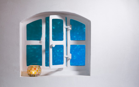 White wall with open arched window with blue glow outside and candle burning in bowl on the sill. Copy space Stock fotó