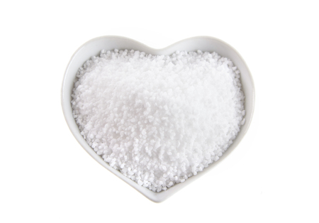 Heart shaped bowl of fleur de sel salt isolated on white formed on the surface of seawater by evaporation Imagens