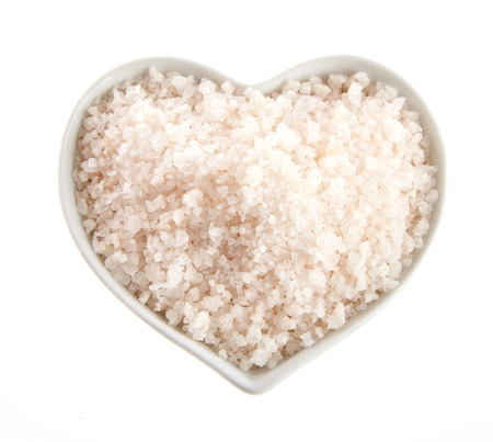 Heart-shaped bowl of Himalaya rock salt or halite isolated on white viewed from overhead suitable for advertising Reklamní fotografie