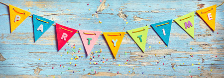 Party Time bunting on wooden background with peeling old blue paint, decorated with colorful confetti. Celebration banner background