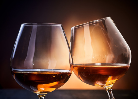 Two glasses of cognac clinking in close-up against dark brown background