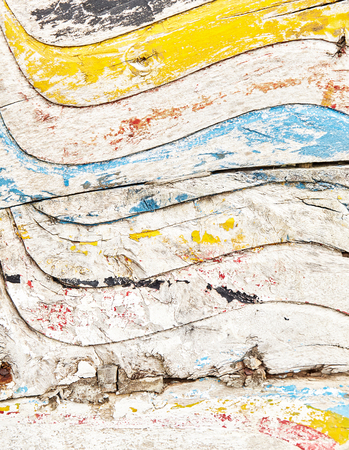 Remains of bright old painting on wooden surface with peeling paint from wavy decorations. Rough wooden texture as full frame artistic background concept