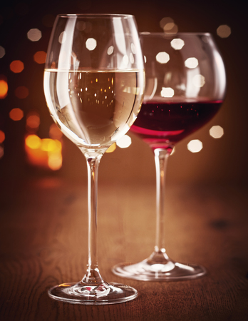 Two glasses of white and red wine in close-up, with festive lights blurred in bokeh effect at night in background. Party concept