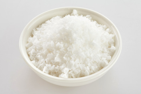 Bowl of white Portuguese flor de sal, a salt derived from the evaporation of sea water and rich in minerals over white Stock fotó