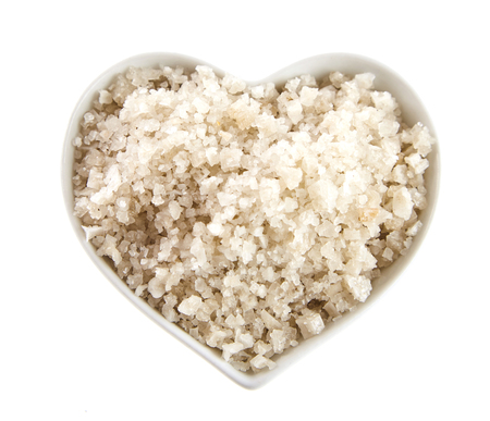 Unadulterated French Guerande sea salt from Brittany served in a small heart shaped bowl over white viewed from above Stock Photo
