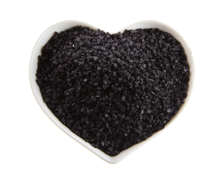 Heart-shaped bowl of black lava salt from Hawaii made from marine salt blended with activated charcoal in an overhead view on white