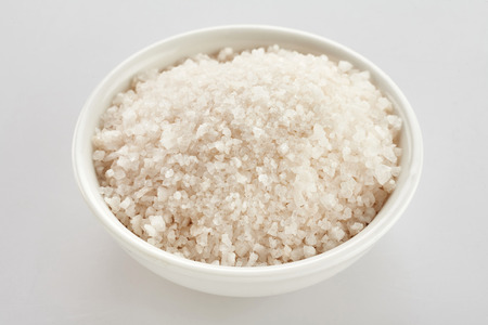 Bowl of coarse ground white kitchen salt for cooking over a white background in a close up view