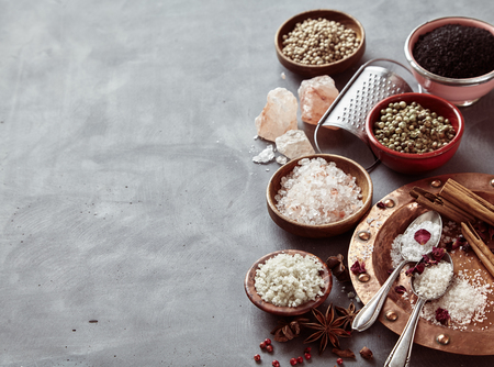Border of natural cooking salts from around the world and aromatic spices on a mottled grey background with copy space Imagens