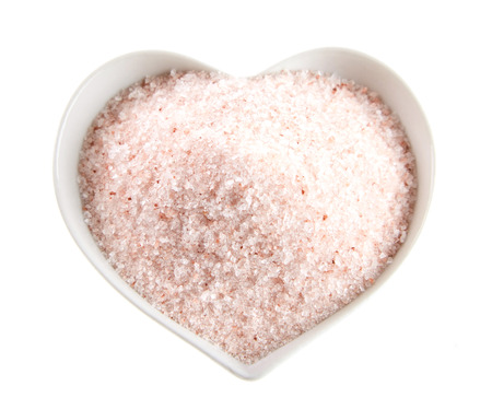 Pink Indus mountain salt from Pakistan in a heart shaped bowl isolated on white viewed top down