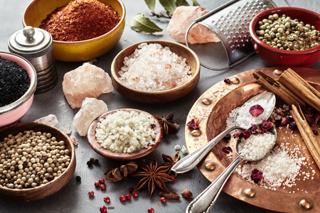 A variety of natural cooking salt in bowls with peppercorns, herbs and spices in a full frame culinary still life on grey