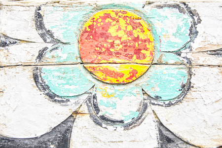Flower painted on wooden surface with peeling paint, viewed in close-up and full frame. Background concept