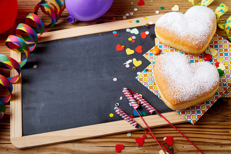Easter treats and decorations with copy space on blackboard in wooden frame on the table with heart-shaped cookies, confetti and firecrackers, viewed in close-up from high angle Stock Photo