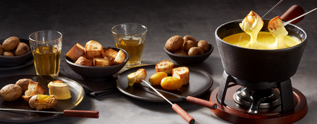 Panorama banner of a cheese fondue and sides with two forks with toasted bread being dipped in the sauce in a cast iron pot on a burner Stock Photo