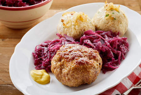 German frikadellen, a spicy meatball of minced beef or veal with dumplings and shredded red cabbage on an oval plate