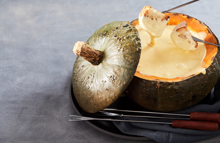Creamy cheese fondue for entertaining with two dipping forks coated in sauce served in a hollow pumpkin or seasonal squash over grey with copy space