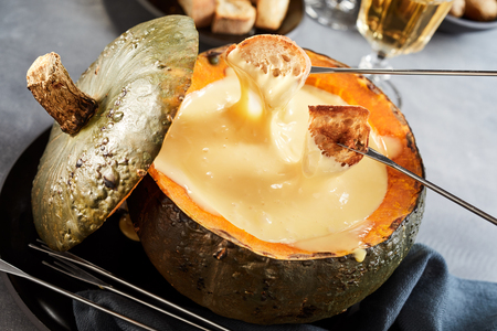 Creamy cheese fondue served in a pumpkin or gourd for a delicious traditional autumn meal viewed close up high angle suitable for a menu