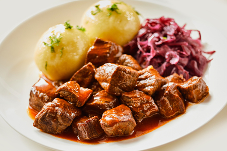 Wild venison goulash or hot pot served with dumplings and red cabbage in a close up side view for advertising Zdjęcie Seryjne