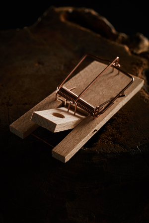 Wooden spring type mouse trap on black with copy space with the spring pulled back in readiness but no cheese as bait