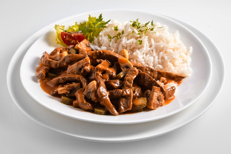 Serving of German pork ragout in a rich gravy served with fluffy rice in a close up view suitable for a menu 스톡 콘텐츠