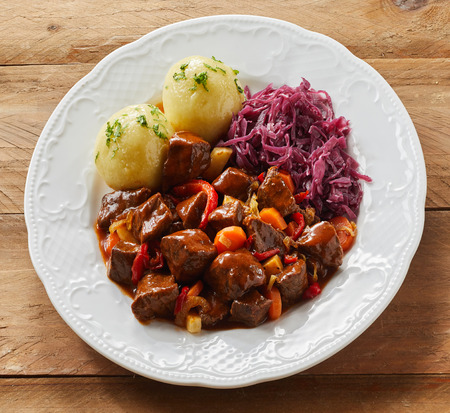 Plate of wild deer or venison goulash with shredded red cabbage and dumplings for a tasty German or Bavarian meal in square format