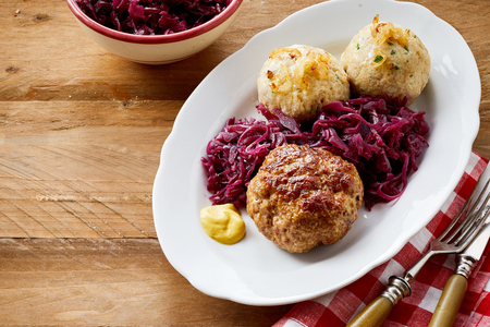 German meatball and dumplings served with red cabbage sauerkraut and a dollop of mustard on an oval platter