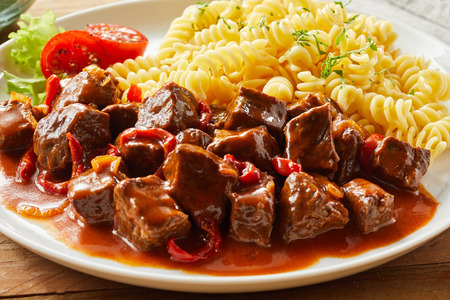Spicy wild game goulash with deer venison served with pasta noodles in a close up view for a menu