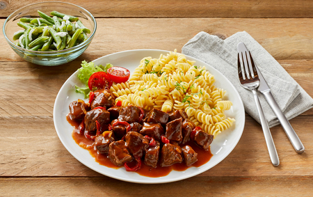 Venison goulash or stew with diced wild boar and deer served with noodles and fresh green beans