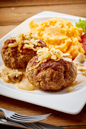 Two seasoned Bavarian frikadellen or ground beef and veal meatballs with onion topping and carrot and potato blend accompaniment
