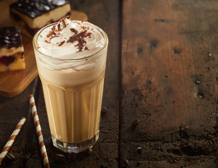 High glass of frothy cappuccino coffee with chocolate topping served with cake and candies on old dark wooden table. Copy space