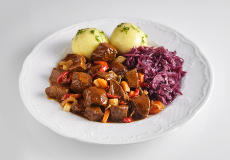 Tasty gourmet wild boar and deer venison goulash served with German dumplings and red cabbage on a white dish