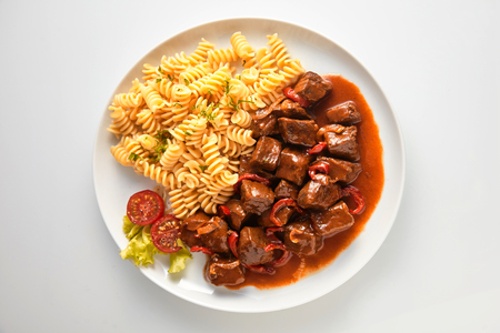 Wild venison stew or goulash with boar and deer meat in a rich spicy gravy served with fusilli Italian noodles and tomato garnish
