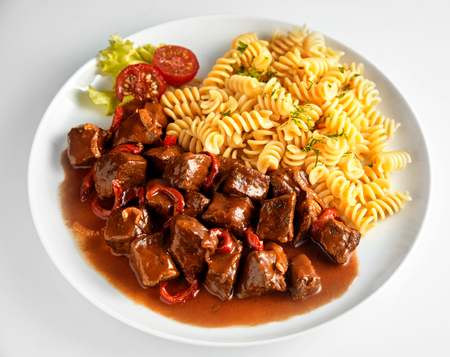 Wild deer venison goulash with fusilli pasta served on a white plate viewed high angle for a menu or advertising Standard-Bild