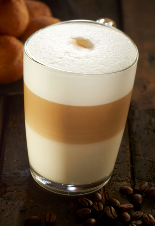 Frothy layered cappuccino in glass mug viewed in close-up from high angle, with coffee beans on dark wooden table 写真素材