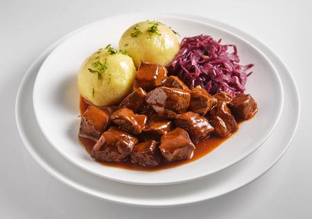 Wildschwein- und Hirscheintopf oder Gulasch mit Fleischwürfeln in einer reichhaltigen Sauce serviert mit Knödeln und geriebenem Rotkohl auf einem weißen Teller