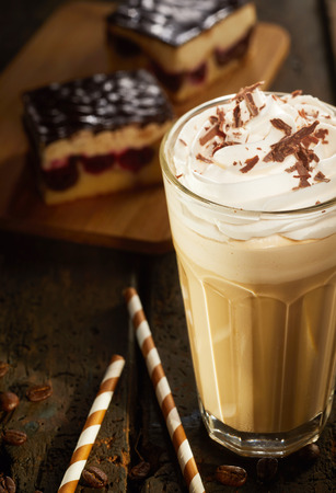Cappuccino in high glass with chocolate topping served with chocolate cake and candies on dark old wooden table. Viewed in close-up from high angle Stock Photo