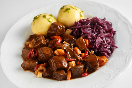 Spicy wild boar or venison goulash in a rich gravy served with dumplings and red cabbage on a white plate Stock Photo