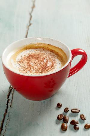 Taza de café rojo con espuma, servido en una mesa de madera antigua en primer plano desde un ángulo alto Foto de archivo