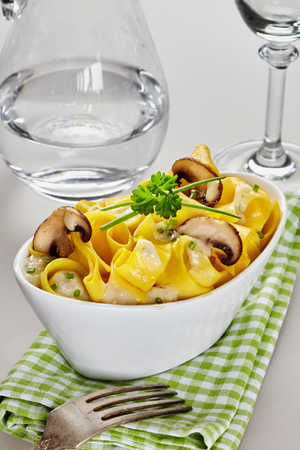 Italian pasta with fresh sliced grilled mushrooms and cheese garnished with parsley and chives served in a stylish white dish on a checkered green napkin