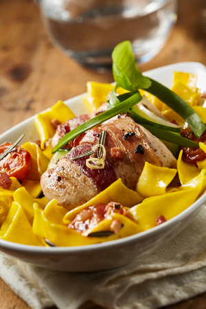 Pork fillet wrapped in ham on a bed of ribbon noodles with roasted tomatoes and fresh green herbs
