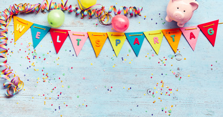Festive flag bunting with WeltSparTag text, or world savings day, with piggy bank, party streamers, balloons and confetti scattered on blue wood with copy space 스톡 콘텐츠