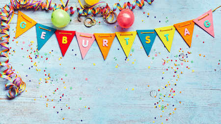Geburtstag or Birthday party background with streamers and balloons above a string of colorful bunting with German text and copy space below on blue wood