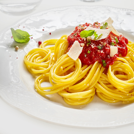 Italian spaghetti pasta with tomato sauce dressing seasoned with spices and fresh herbs and garnished with parmesan cheese